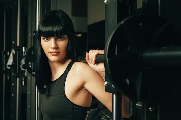 Geschikte vrouw die hurkzit in een machine van smith in gymnastiek doen