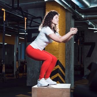 Geschikte vrouw die hurkzit op houten doos in gymnastiek doet