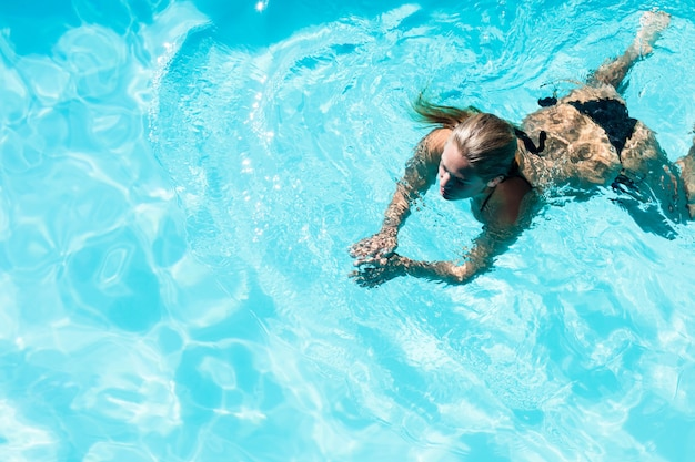 Geschikte vrouw die in het zwembad op een zonnige dag zwemt