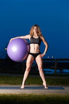 Geschikte vrouw die oefeningen met geschikte bal doet