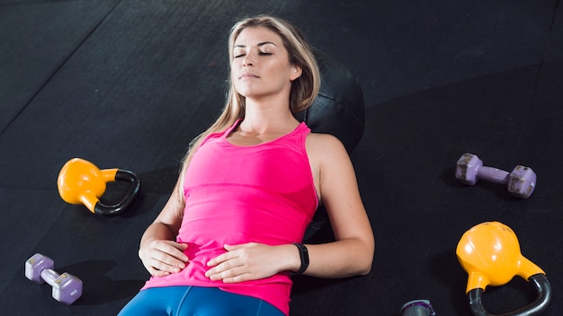 Geschikte vrouw die op vloer dichtbij oefeningsmateriaal rusten