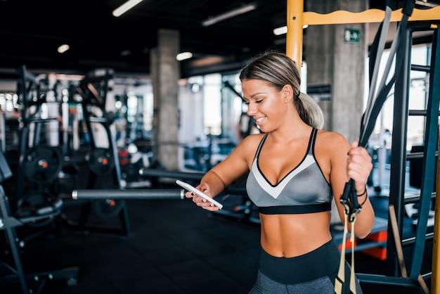 Geschikte vrouw die smartphone in de gymnastiek gebruiken.
