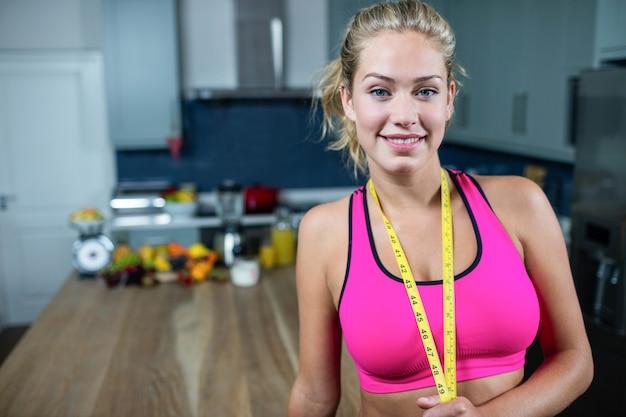 Geschikte vrouw die sportbustehouder in de keuken draagt