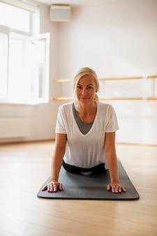 Geschikte vrouw die yogaposities uitoefent