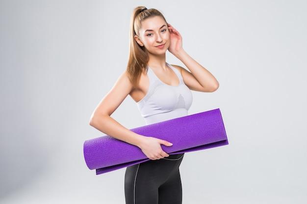 Geschikte vrouw met een geïsoleerde gymnastiekmat