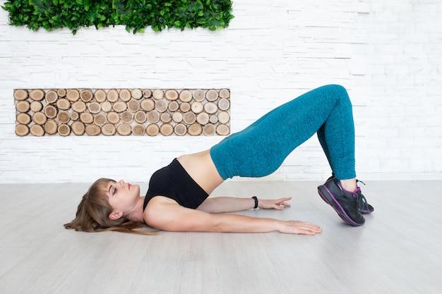 Geschikte vrouwen die op de vloer liggende sportkleding dragen, doen oefeningen om spieren op te bouwen