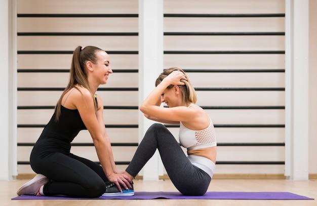 Geschikte vrouwen die samen bij de gymnastiek uitoefenen