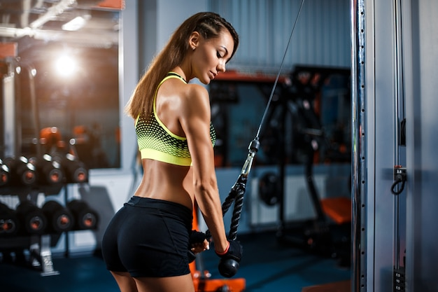 Geschikte vrouwentraining triceps die gewichten in gymnastiek opheffen