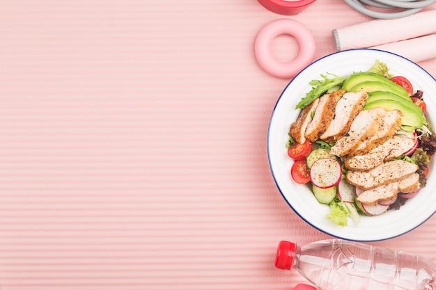 Geschiktheid en een actieve gezonde levensstijl concept. bord met kipfilet salade