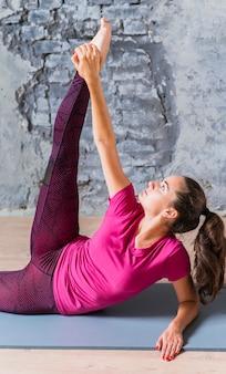 Geschiktheids jonge vrouw die op oefeningsmat leunt die haar benen uitrekt