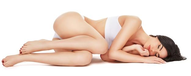 Geschiktheids jonge vrouw met een mooi lichaam dat op witte muur legt