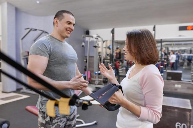 Geschiktheidsinstructeur en rijpe vrouw bij gymnastiek.