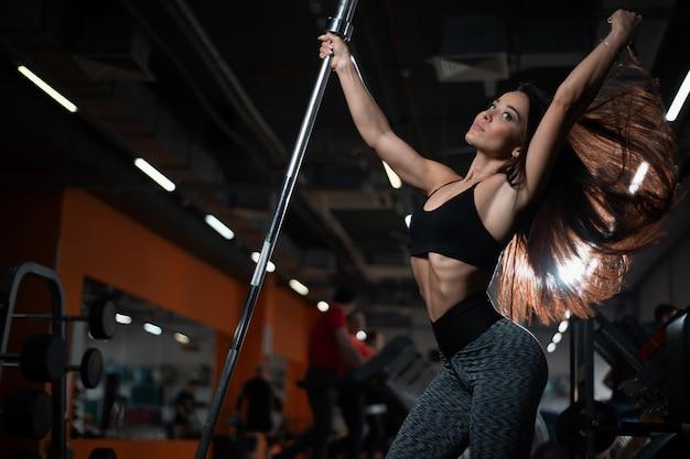 Geschiktheidsmeisje het stellen in de gymnastiek, die met haar mooi haar en lichaam pronkt