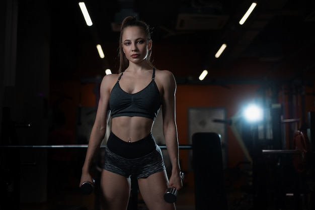 Geschiktheidsmeisje het stellen in de gymnastiek met domoren in haar handen, die met haar lichaam pronken