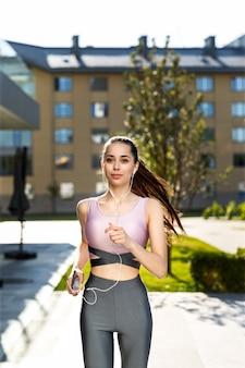 Geschiktheidsmeisje in de modieuze sportkleding die lopende cardiotraining in de ochtend doen
