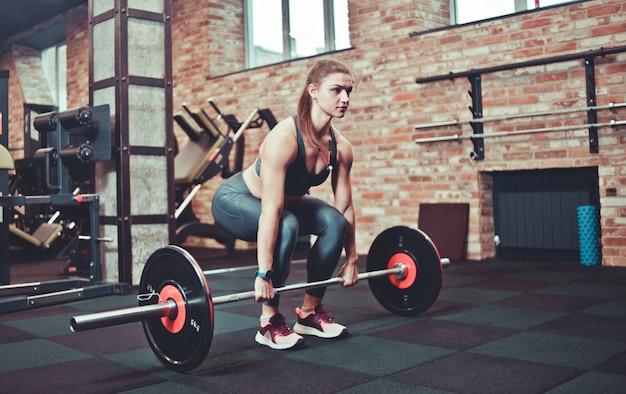 Geschiktheidsmeisje in sportkleding die deadlift oefening met barbell doen bij gymnastiek