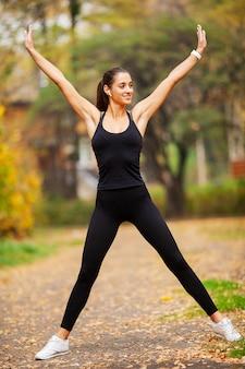 Geschiktheidsmeisje, jonge vrouw die oefeningen in het park doen.