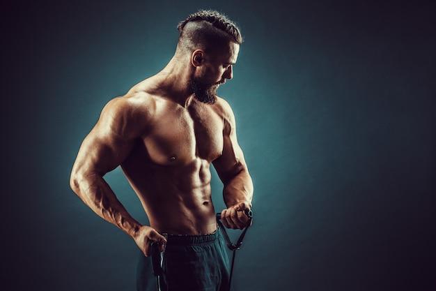 Geschiktheidsmens die met het uitrekken van band uitoefenen. gespierde sport man trainen met elastische rubberen band. kerel die met elastiekje uitwerkt. fit, fitness, lichaamsbeweging, training en een gezonde levensstijl
