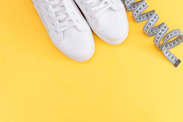 Geschiktheidstoebehoren op een gele achtergrond. sneakers, fles water, oortelefoons en halters.