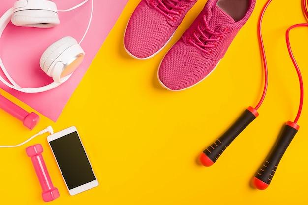 Geschiktheidstoebehoren op gele achtergrond. sneakers, fles water, koptelefoon en smart. bovenaanzicht. stilleven. kopieer ruimte