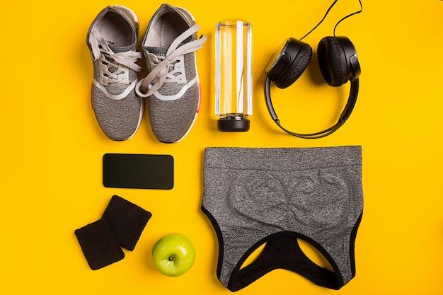 Geschiktheidstoebehoren op gele achtergrond. sneakers, fles water, koptelefoon en sporttop. bovenaanzicht. stilleven