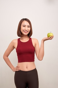 Geschiktheidsvrouw die appel eet die meetlint draagt. fit sportieve multiculturele aziatische / kaukasische vrouwelijke fitness vrouw geïsoleerd op wit. - afbeelding