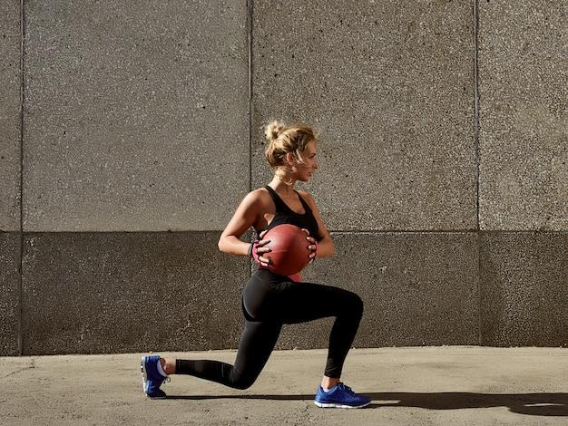 Geschiktheidsvrouw die bij in openlucht gymnastiek uitwerken die geneeskundebal gebruiken.