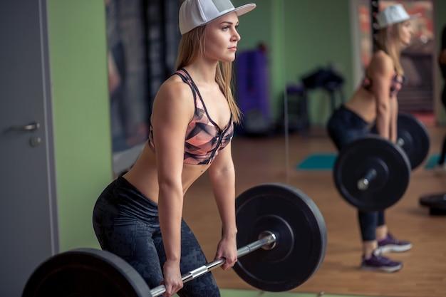 Geschiktheidsvrouw die deadlift met zware gewichten in gymnastiek voorbereidingen treffen te oefenen. het wijfje die zwaargewicht opheffen doen werkt in gezondheidsclub uit.