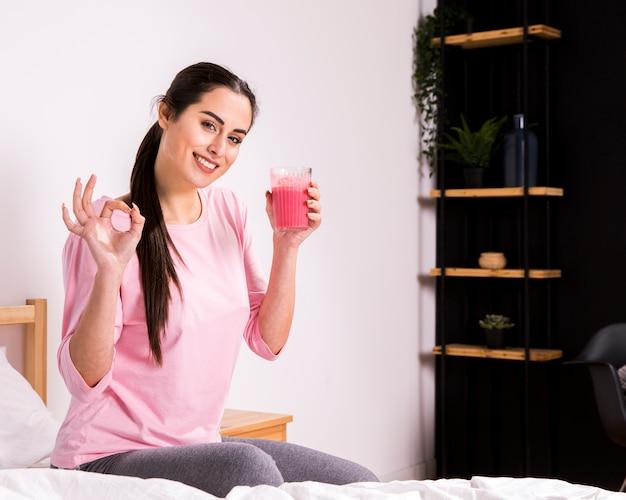 Geschiktheidsvrouw die een detoxsap drinken