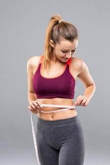 Geschiktheidsvrouw die haar geïsoleerd lichaam meten. gewichtsverlies concepten