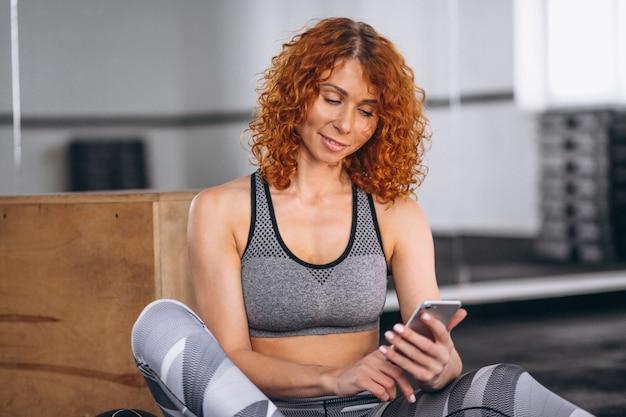 Geschiktheidsvrouw die op de telefoon bij de gymnastiek spreken