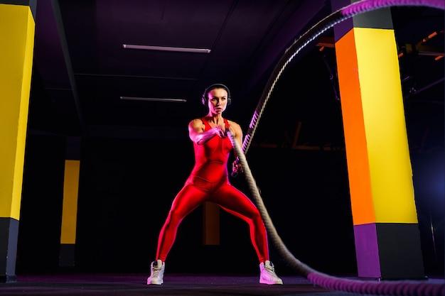 Geschiktheidsvrouw die opleidingskabels voor oefening gebruiken bij gymnastiek. atleet die met strijdtouwen bij gymnastiek uitwerkt