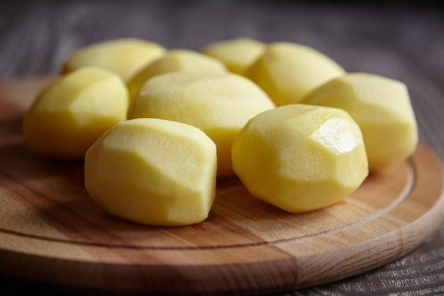 Geschilde aardappelen op houten snijplank op bruine tafel