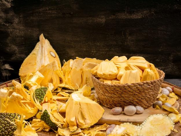 Geschilde jackfruit in wevende mand met zaad en shell op dorsenmand.