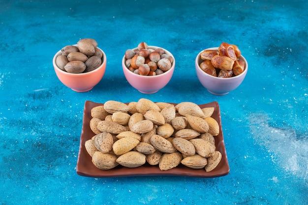 Geschilde noten in een bord en kommen op het blauwe oppervlak