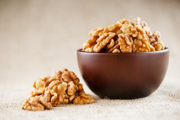 Geschilde walnoten in een houten, donkerbruine kop op een jute doek.