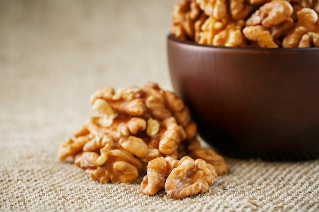 Geschilde walnoten in een houten, donkerbruine kop op een jute doek