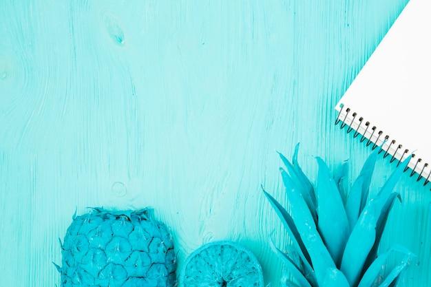 Geschilderd azuurblauw tropisch fruit en notitieblok