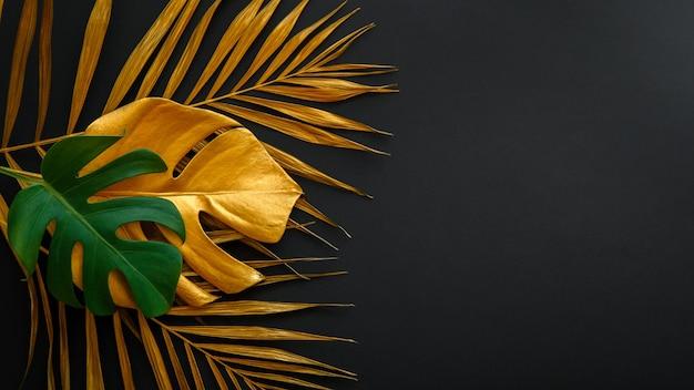 Geschilderd bladgoud bos patroon op zomer natuur bloemen zwarte achtergrond. gouden palmblad en groene verse tropische monstera verlaten textuurframe op donkere zwarte lay-out. lange webbanner kopie ruimte.