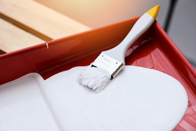Geschilderd gereedschap met kwast en verfroller op verfbak om te schilderen