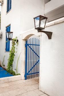 Geschilderde blauwe poorten in witte muur met gaslamp in griekse stijl