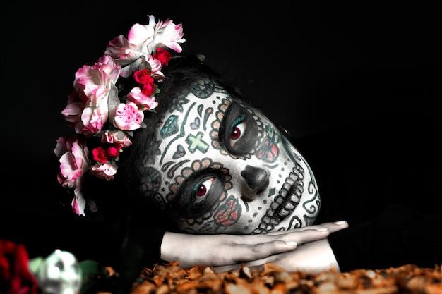 Geschilderde catrina-vrouw die op haar handen leunt en naar de camera kijkt op zwarte achtergrond, dag van de doden, halloween.