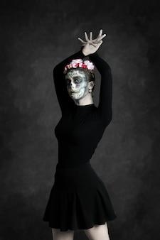 Geschilderde catrina-vrouw en bloemkroon met handen in danspositie op donkere achtergrond, dag van de doden, halloween.