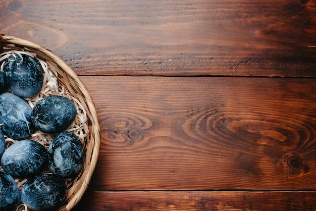 Geschilderde geweven blauwe eieren voor de viering van pasen in een mand op een houten achtergrond