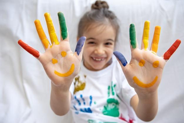 Geschilderde glimlach op de handpalmen van een klein meisje. grappige heldere tekeningen op de handpalmen van kinderen. Premium Foto