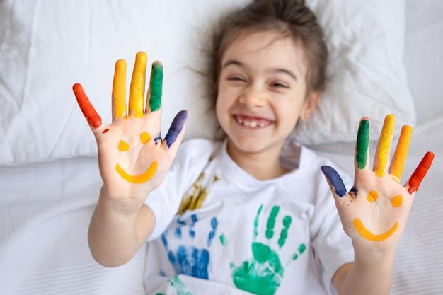 Geschilderde glimlach op de handpalmen van een klein meisje in een t-shirt met gekleurde handafdrukken