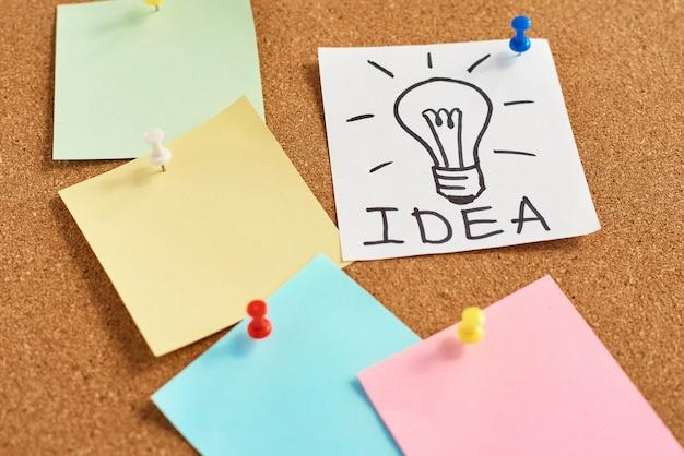 Geschilderde gloeilamp met woordidee en gekleurde lege nota's op een cork raad