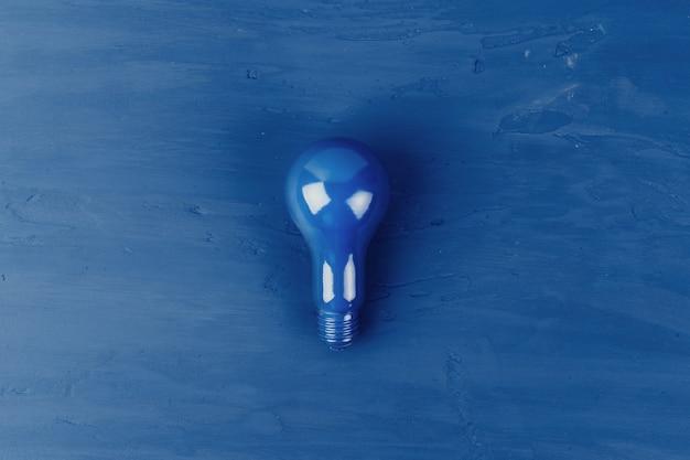 Geschilderde gloeilamp op klassieke blauwe achtergrond, bovenaanzicht