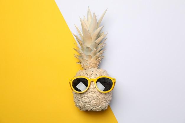 Geschilderde gouden ananas met zonnebril op tweekleurige achtergrond, ruimte voor tekst