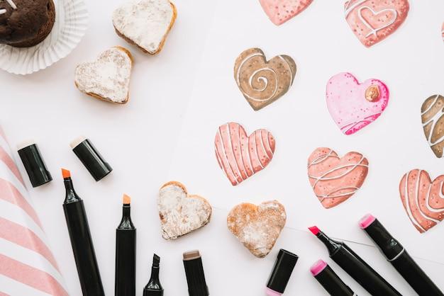 Geschilderde harten op papier dichtbij reeks tellers en koekjes